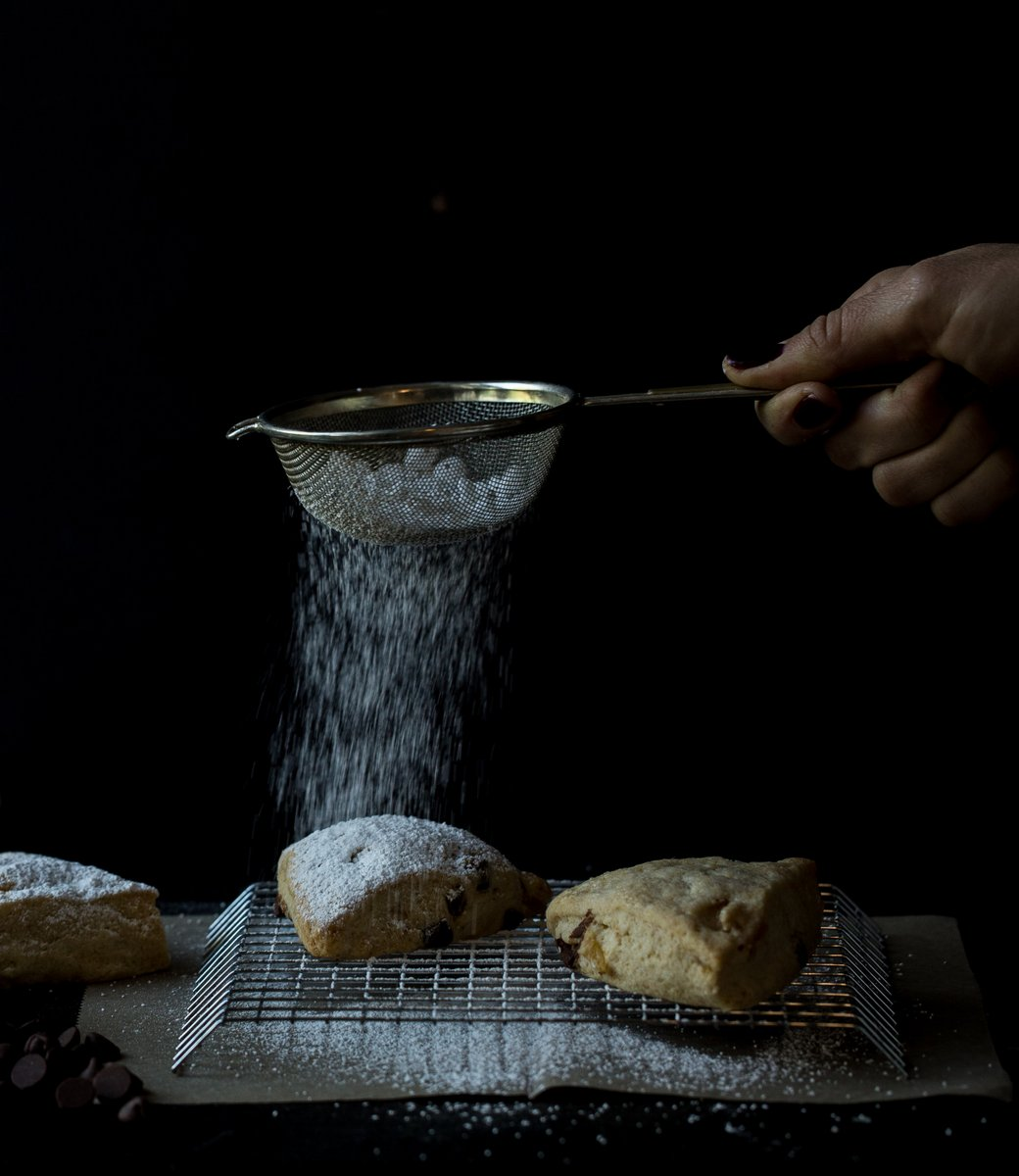 powdered sugar over scones dark moody food photo