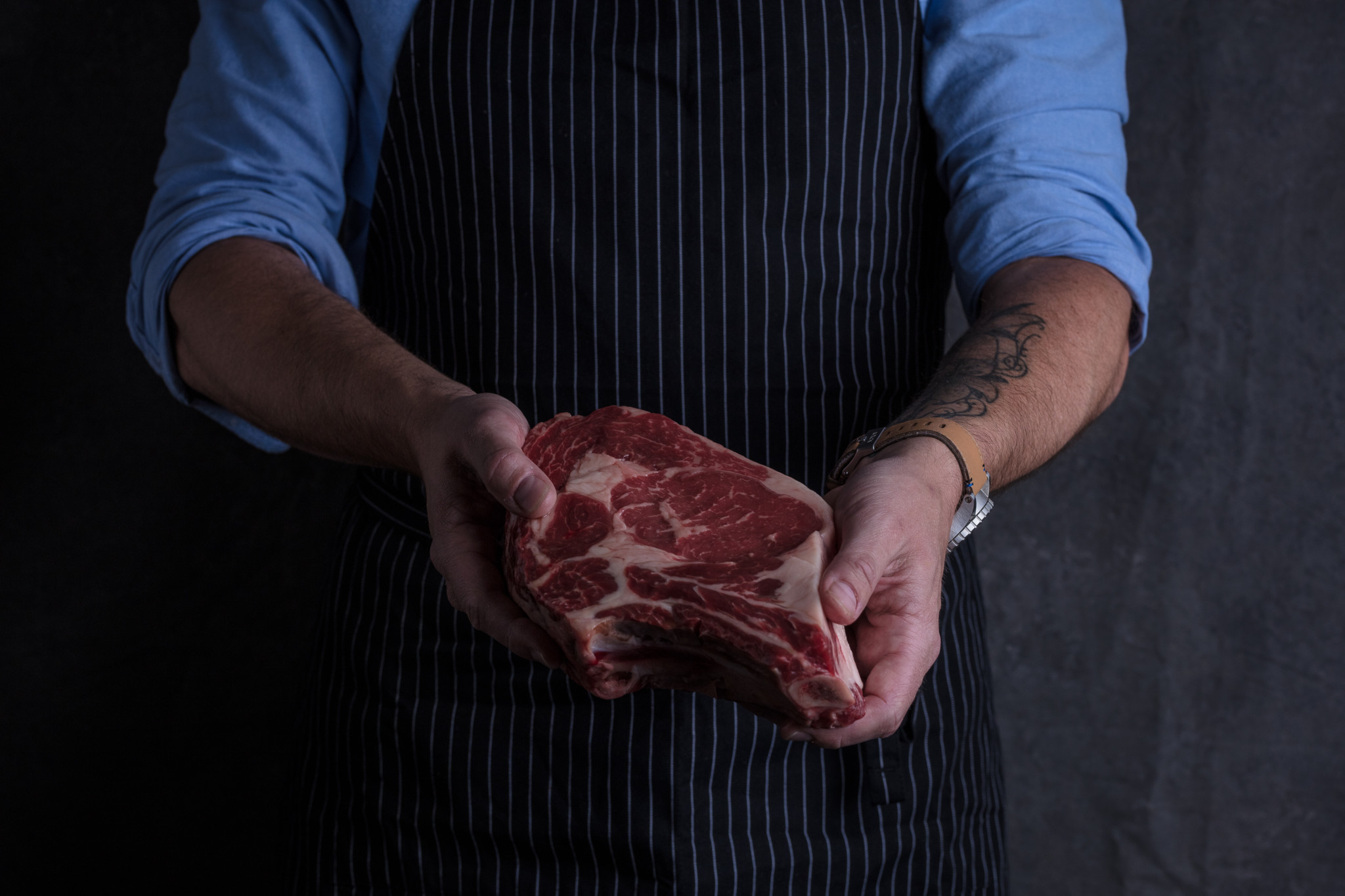butcher holding fresh meat dark background